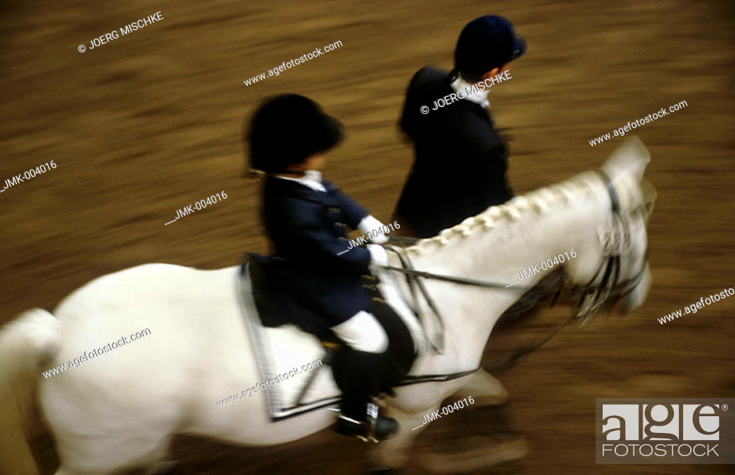 Stock Photo: A little child, 5-10 years old, riding a horse at a horse show, the horse is leaded by an adult.