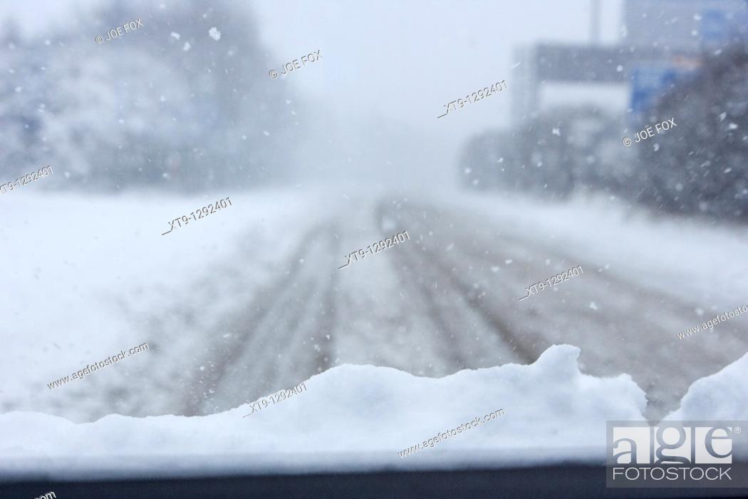 Stock Photo: car with snow on the bonnet driving along a cold frozen road on a cold snowy winters day Belfast Northern Ireland.
