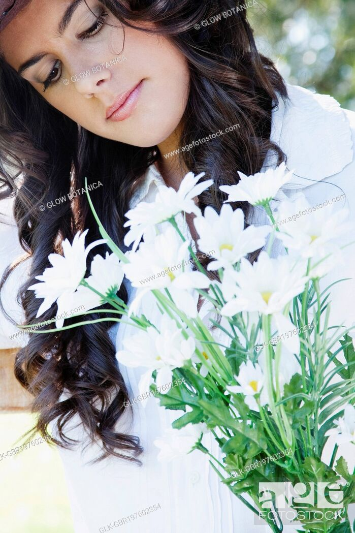 Stock Photo: Woman smelling flowers.