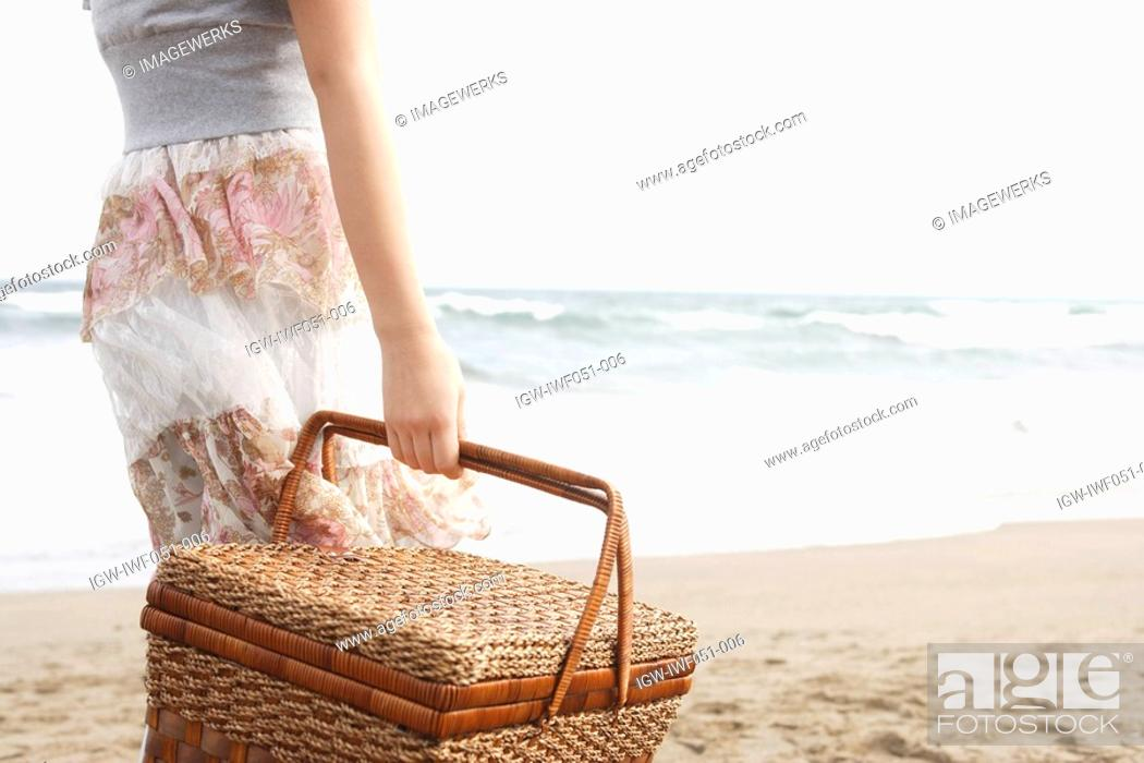 Stock Photo: Teenage girl 14-15 with picnic basket at beach, midsection.