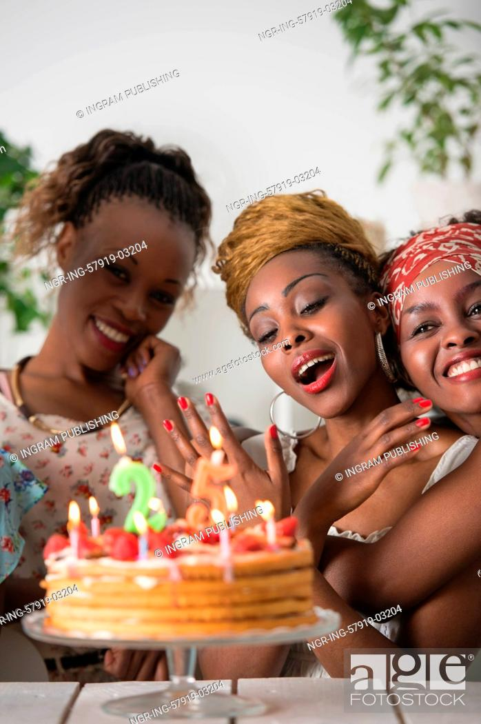 Stock Photo: Portrait of joyful african girl looking at birthday cake surrounded by friends at party.
