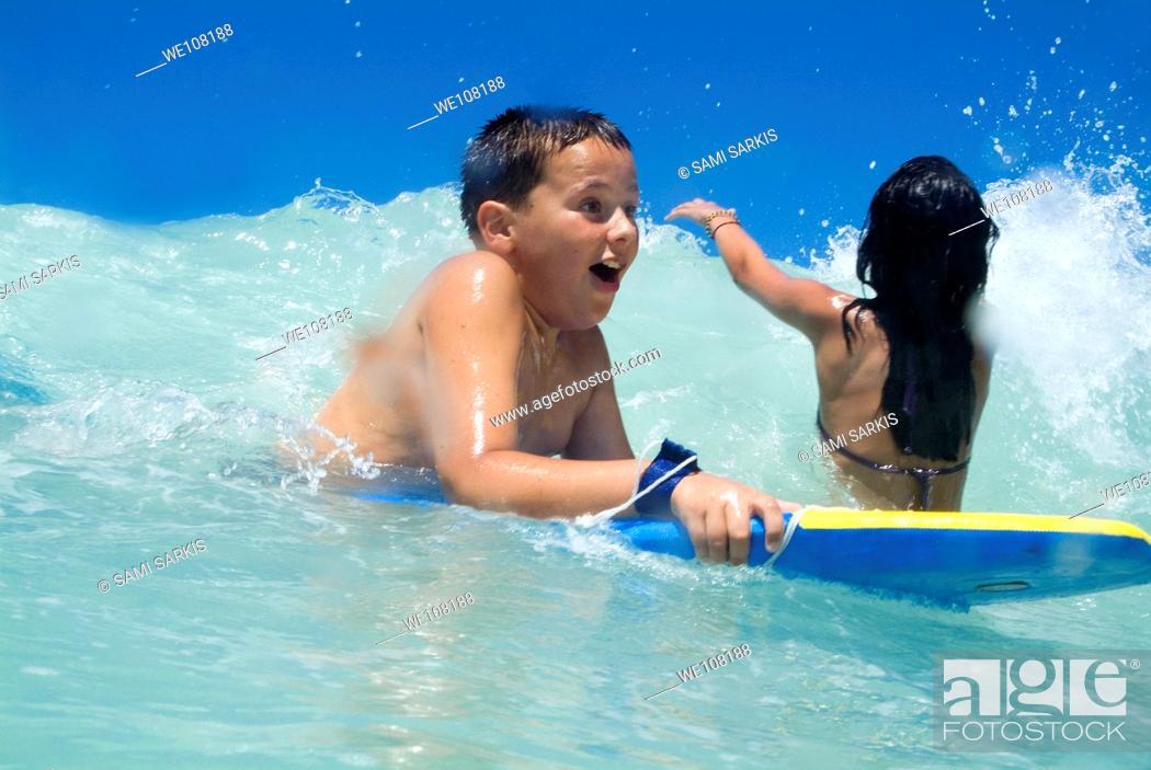 Stock Photo: Children body boarding at surf beach, France.