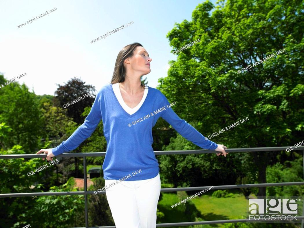 Stock Photo: Woman enjoying the sun, on the terrace.