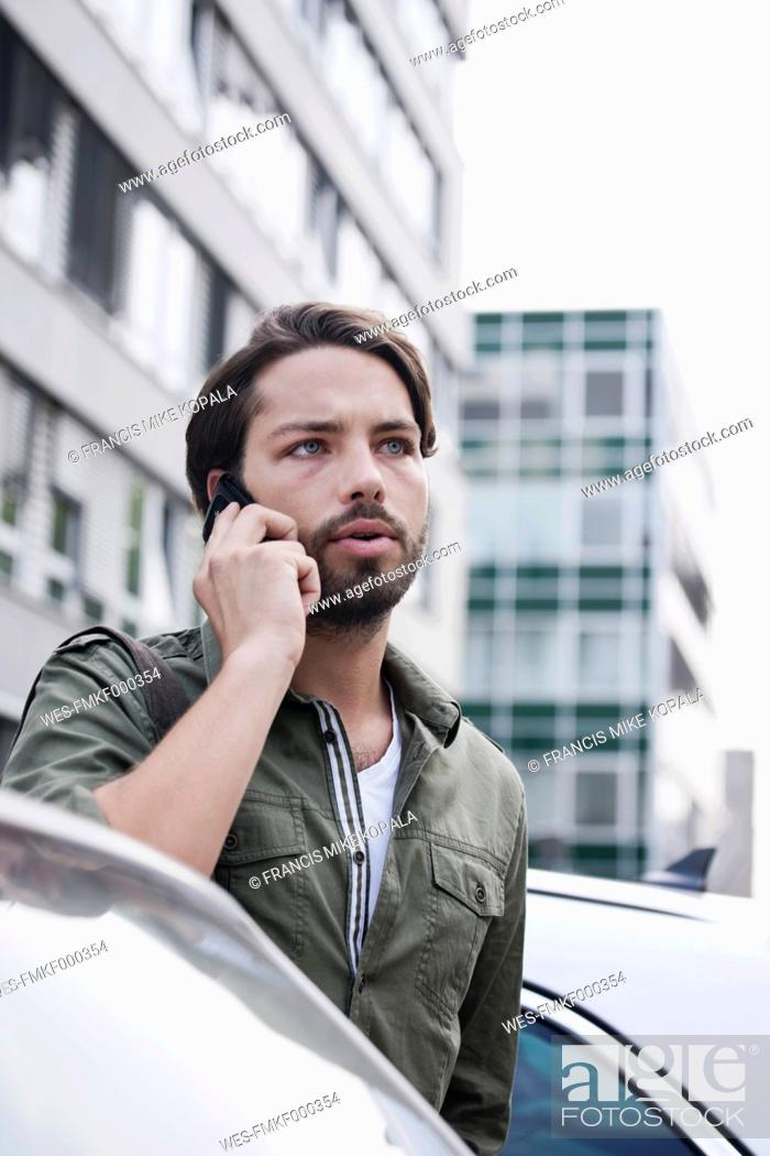 Stock Photo: Germany, Cologne, Young man on phone near car.