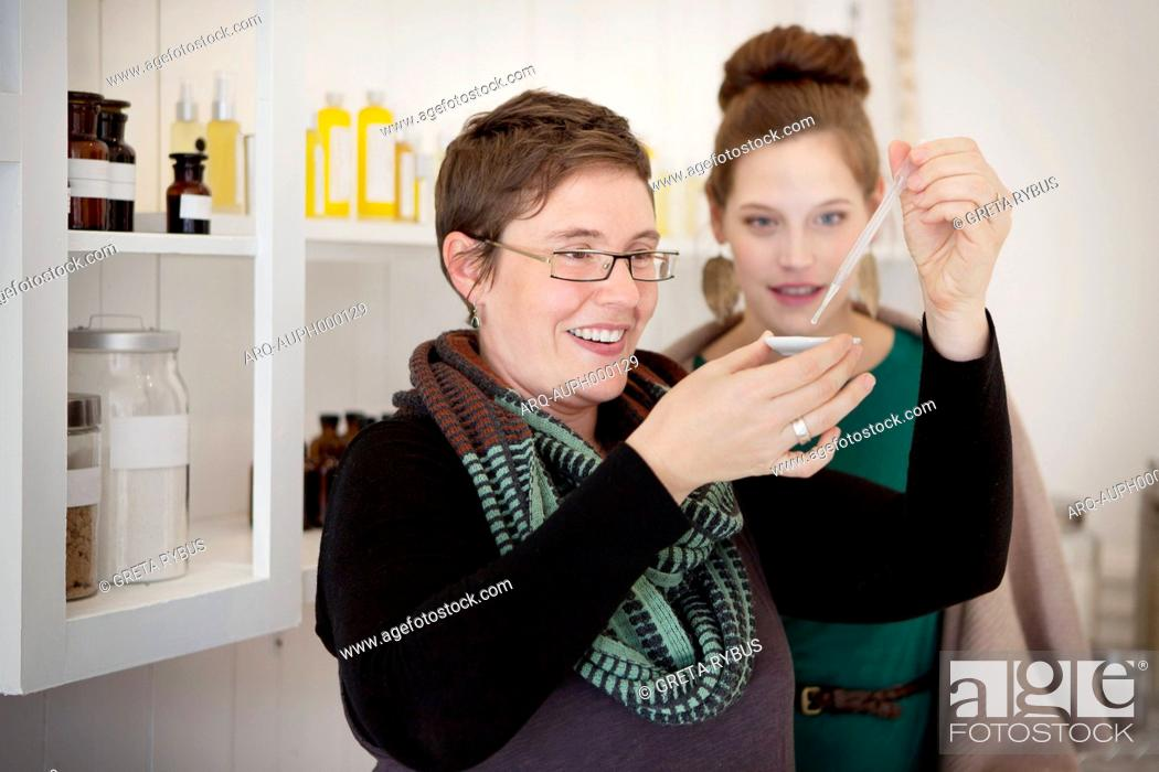 Stock Photo: Sales clerk and customer in perfume store.