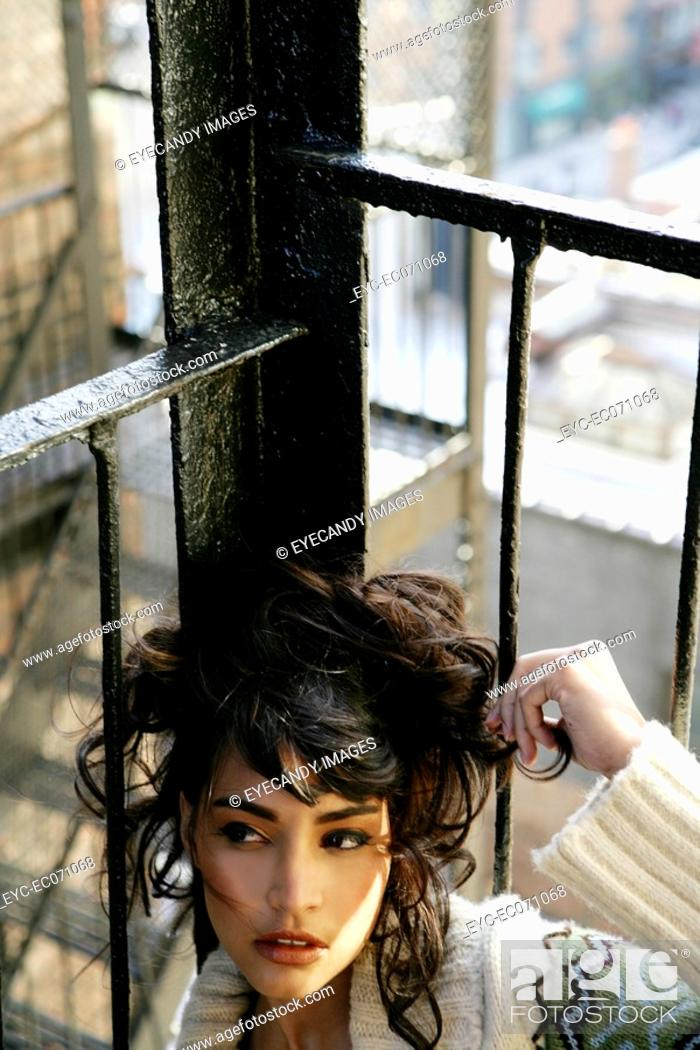 Stock Photo: Young stylish woman sitting on fire escape.