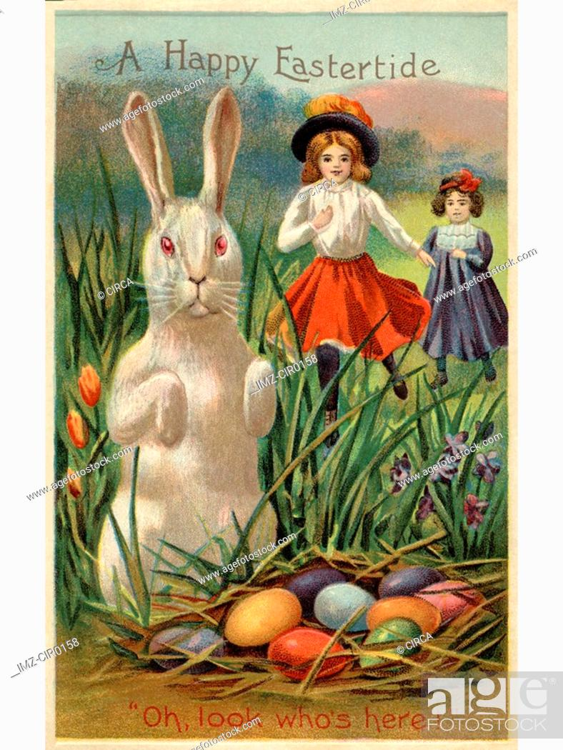 Stock Photo: A vintage Easter postcard of two girls running towards a rabbit and a nest of colored eggs.