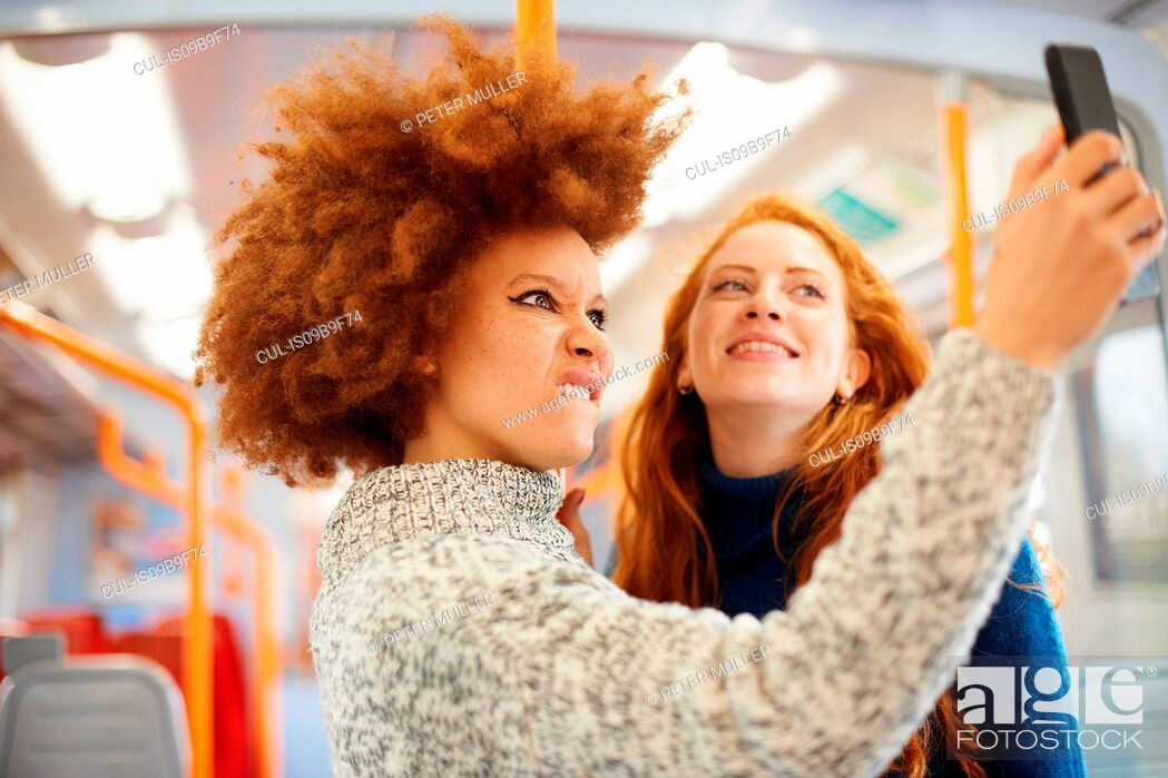 Stock Photo: Friends taking selfie with mobile phone on train, London.