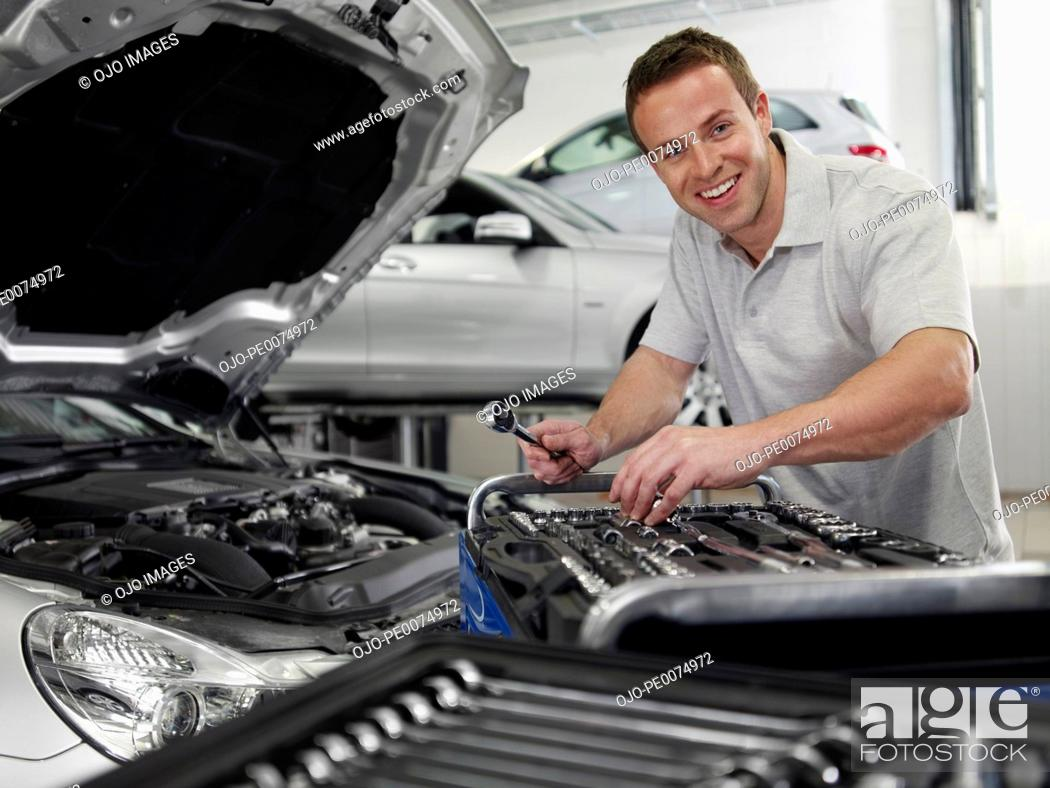 Stock Photo: Mechanic working on car engine.