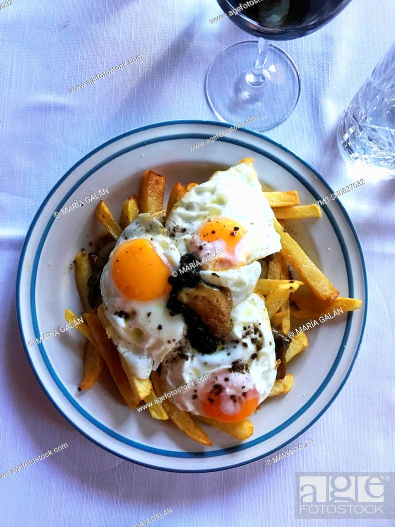 Stock Photo: Fried eggs with potatoes and truffle. View from above.
