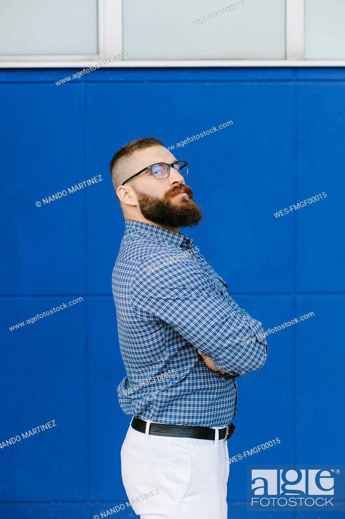 Stock Photo: Portrait of bearded hipster businessman wearing plaid shirt standing in front of blue background.