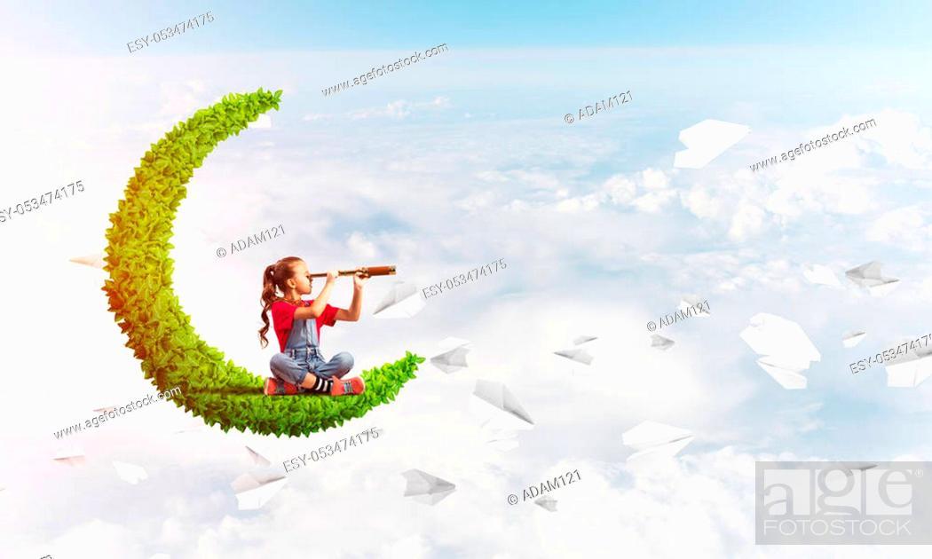 Stock Photo: Cute kid girl on green moon in day sky looking in spyglass.