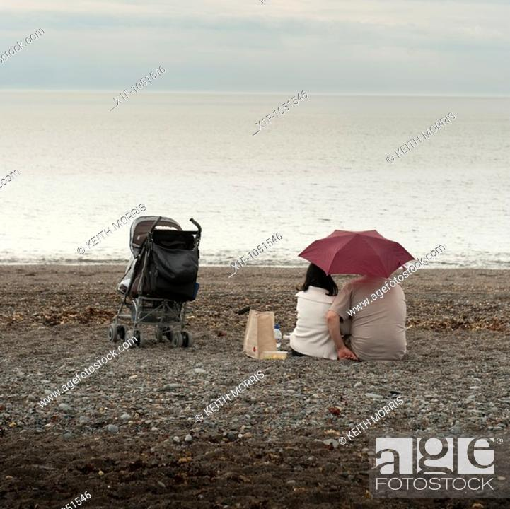 Stock Photo: A young couple sitting under an umbrella on a deserted beach on a typically british wet summer afternoon with a child's buggy next to them  Wales UK.