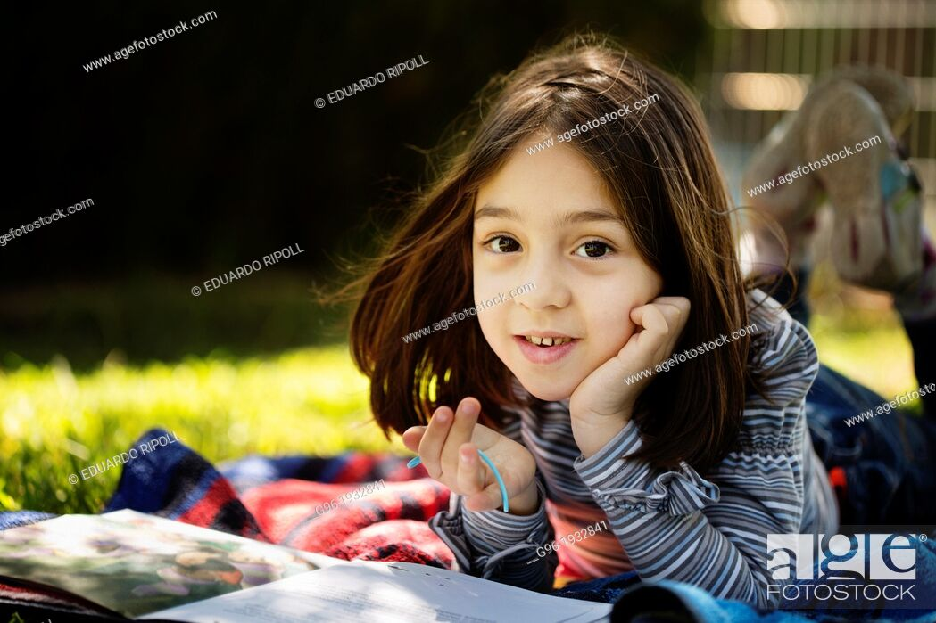 Stock Photo: Girl reading a book on the grass.