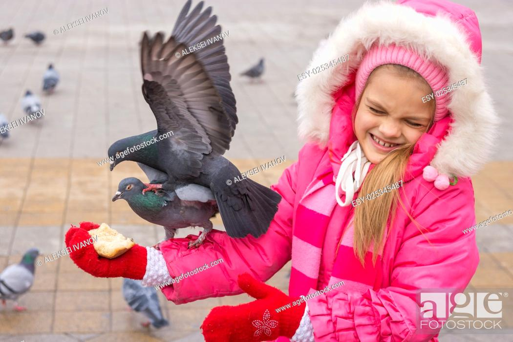 Stock Photo: The girl dodged pigeons, which are fighting for bread.