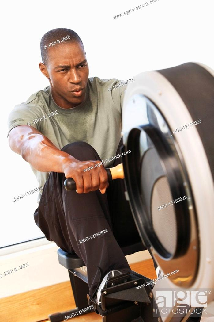 Stock Photo: Man working out on Rowing Machine in health club.