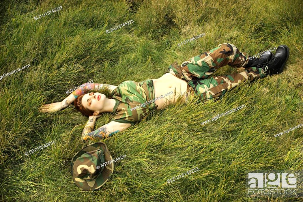 Stock Photo: Tattooed woman in camouflage lying on grass.