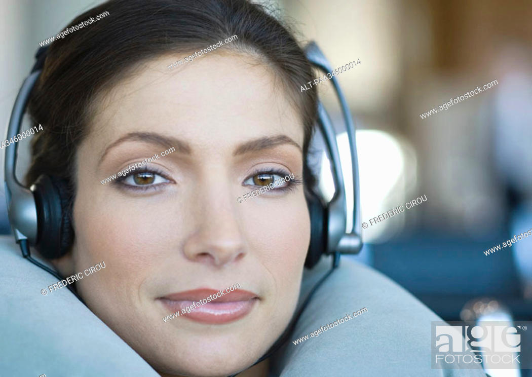 Stock Photo: Woman wearing headphones and using neck pillow, close-up.