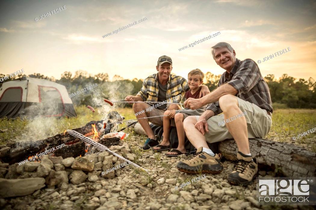 Photo de stock: Three generations of Caucasian men roasting hot dogs over campfire.