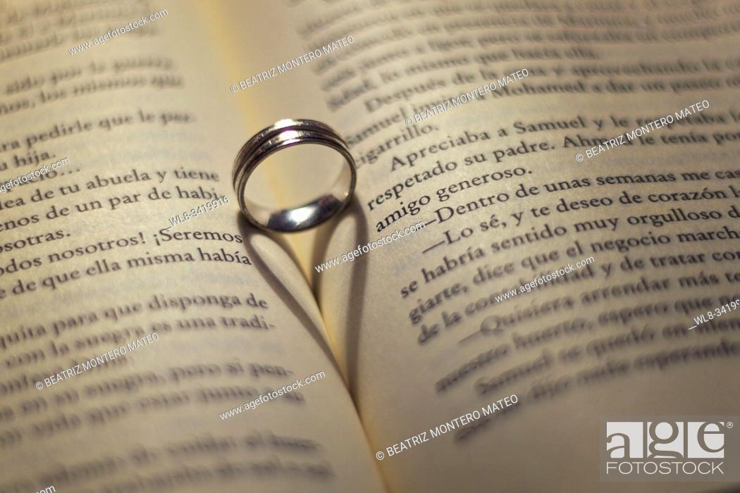 Stock Photo: Heart effect on the book with a ring and light.