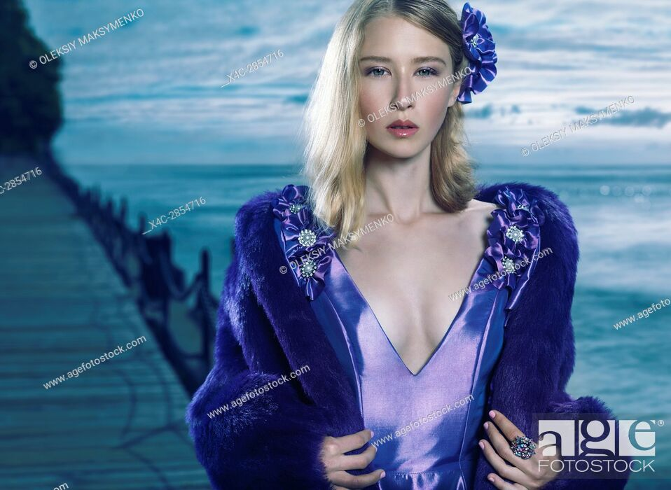Stock Photo: Beauty portrait of a young beautiful blond woman wearing a blue evening dress and a fur jacket outdoors at waterfront.