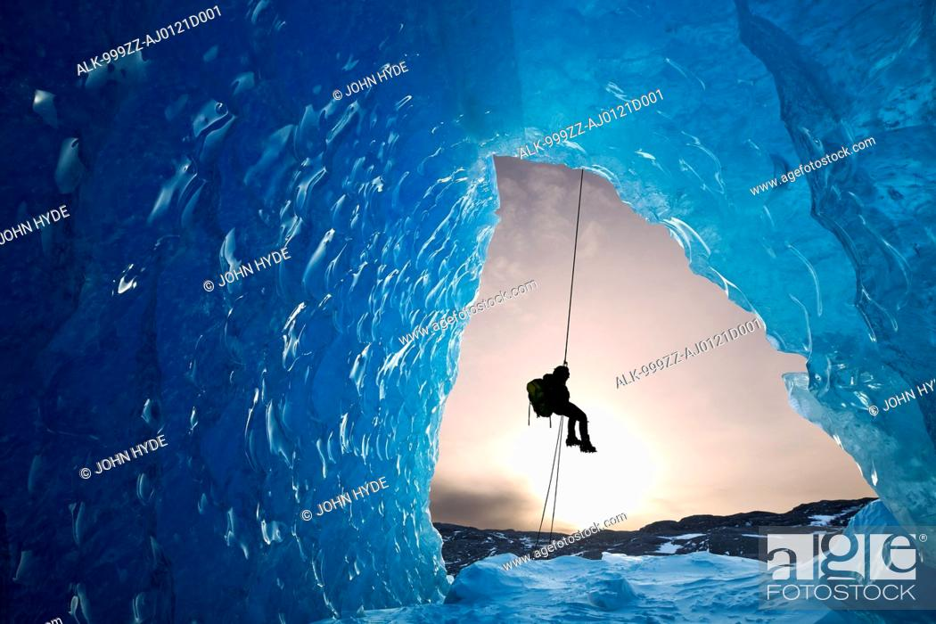 Stock Photo: COMPOSITE: View from inside an ice cave of an iceberg frozen in Mendenhall Lake as an ice climber rappels down a rope, Juneau, Southeast Alaska, Winter.