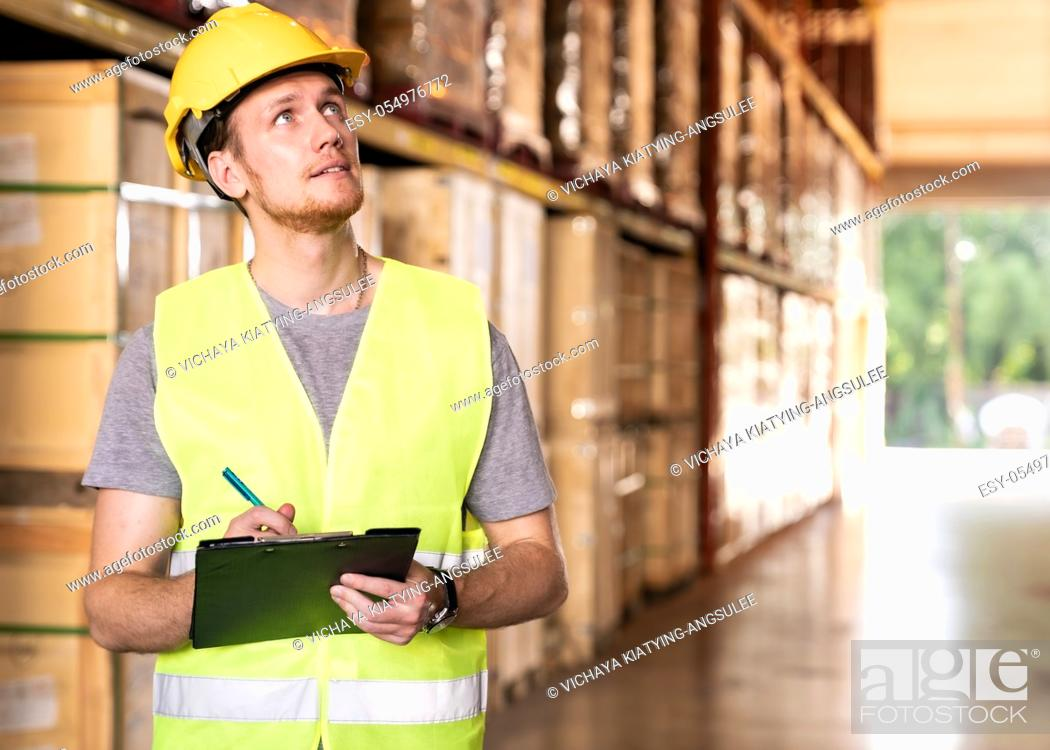 Stock Photo: Portrait white caucasian warehouse worker stand with archboard and pen for inventory checking in large warehouse distribution center.