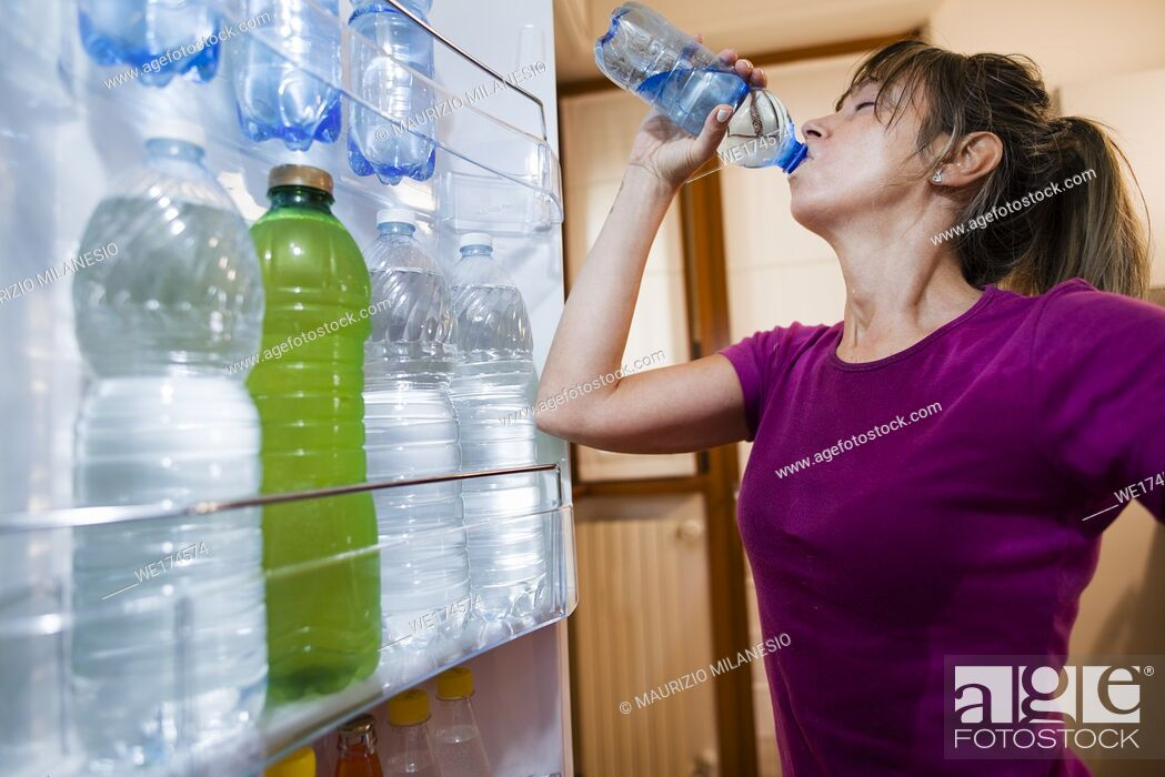 Stock Photo: Sweaty woman drinking water, point of view from inside the open fridge, in the door numerous bottles.