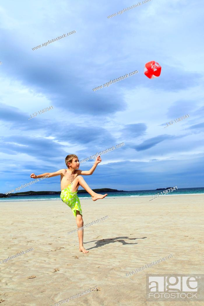 Stock Photo: boy playing on sandy beach, Sutherland, Scotland.