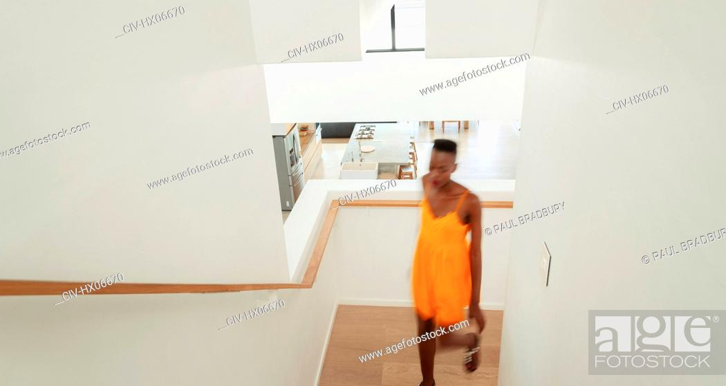 Imagen: Young woman walking up staircase.
