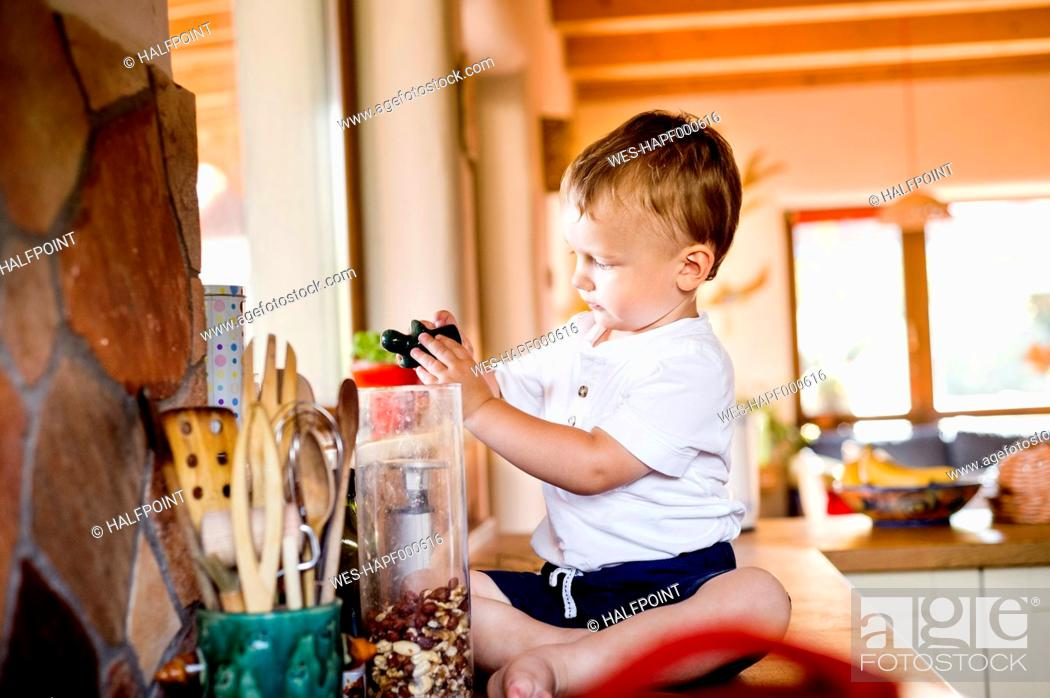 Stock Photo: Little boy is playing in kitchen.