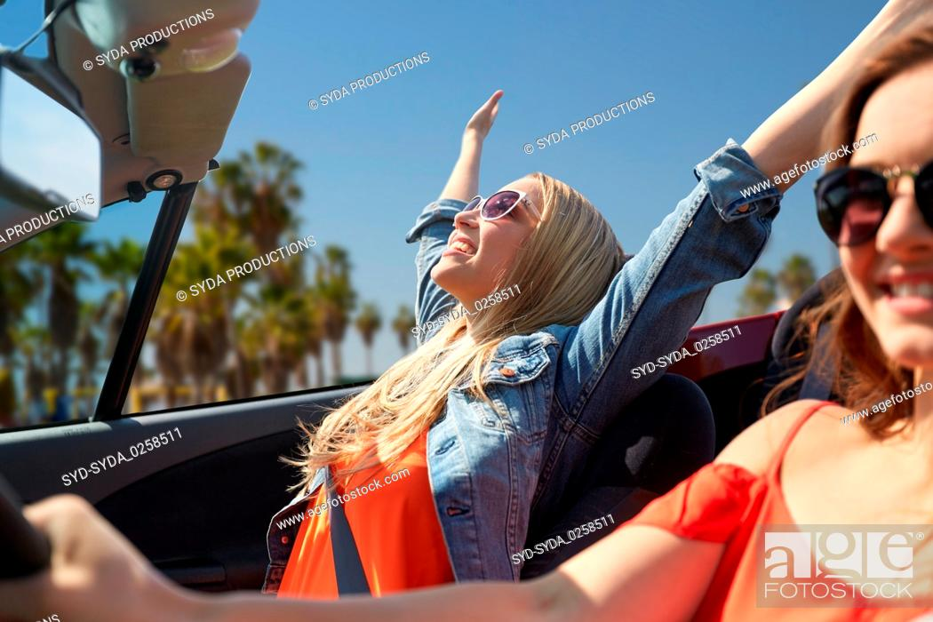 Stock Photo: happy young women driving in car over venice beach.