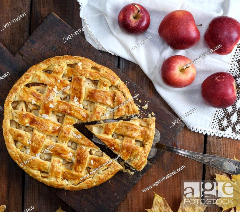 Imagen: baked traditional fruit cake on a brown wooden board and fresh apples on a white textile napkin.
