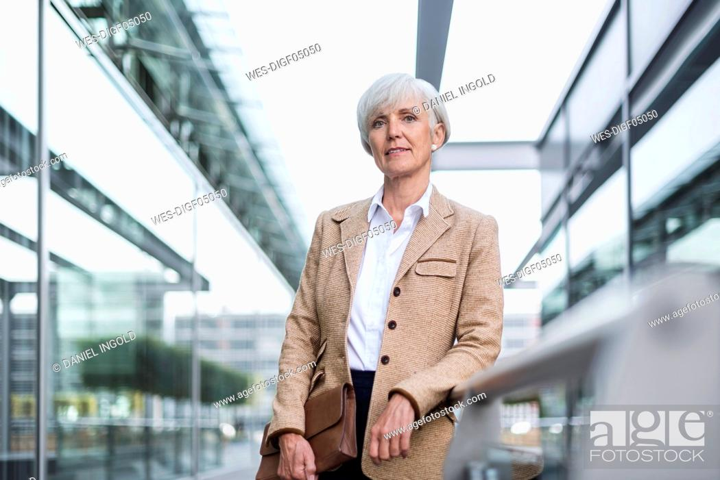 Stock Photo: Portrait of confident senior businesswoman leaning on railing in the city.