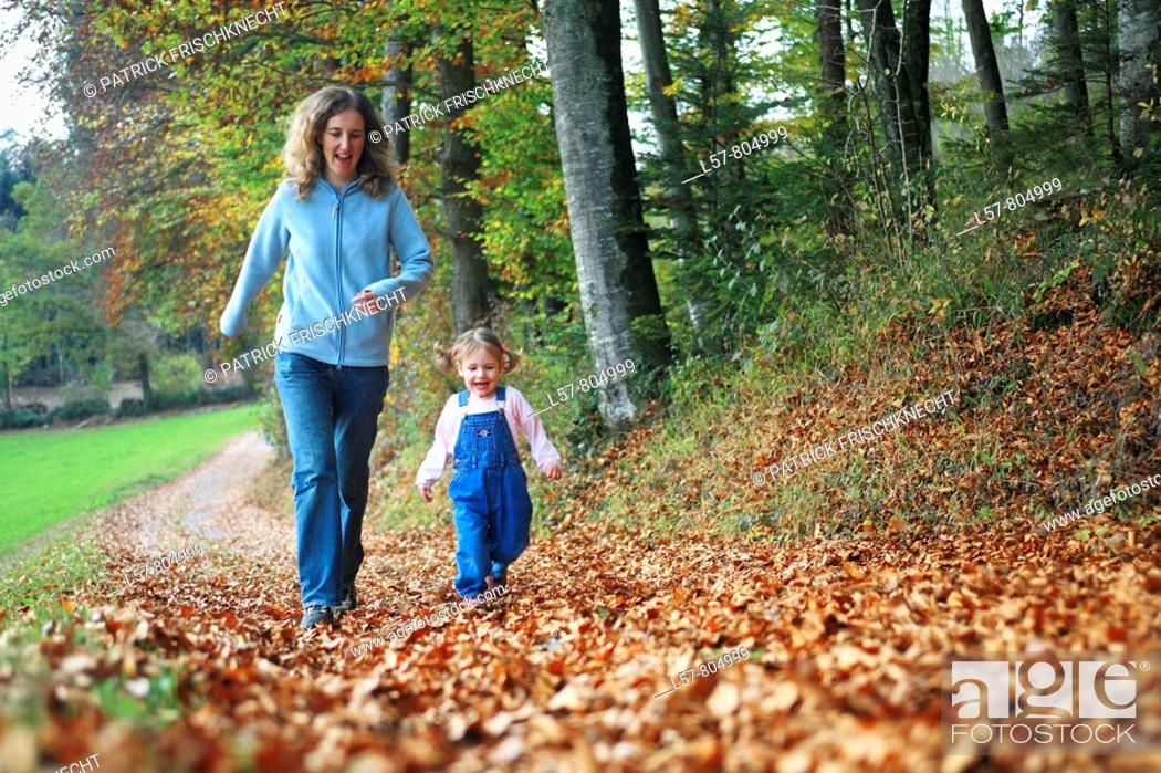 Stock Photo: Mother with daughter running on path full of leaves in fall, having fun and laughing, autumn foliage covering path in forest, autumn, fall, Zuerich, Switzerland.