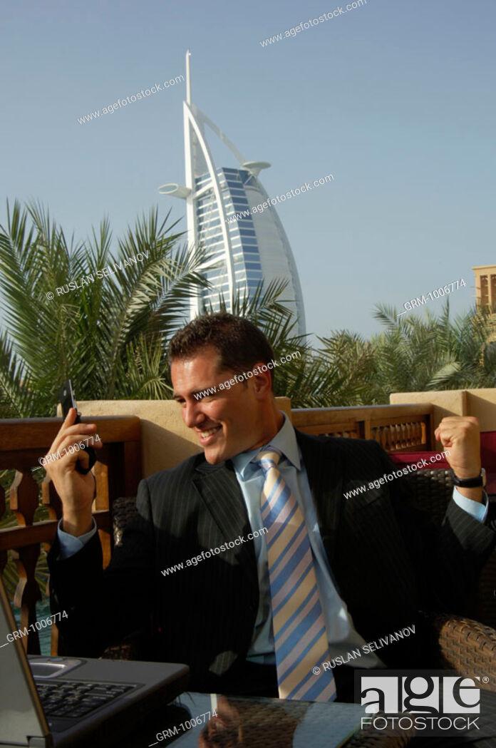 Stock Photo: Happy businessman looking at his mobile phone in Dubai (Burj Al Arab hotel in background).