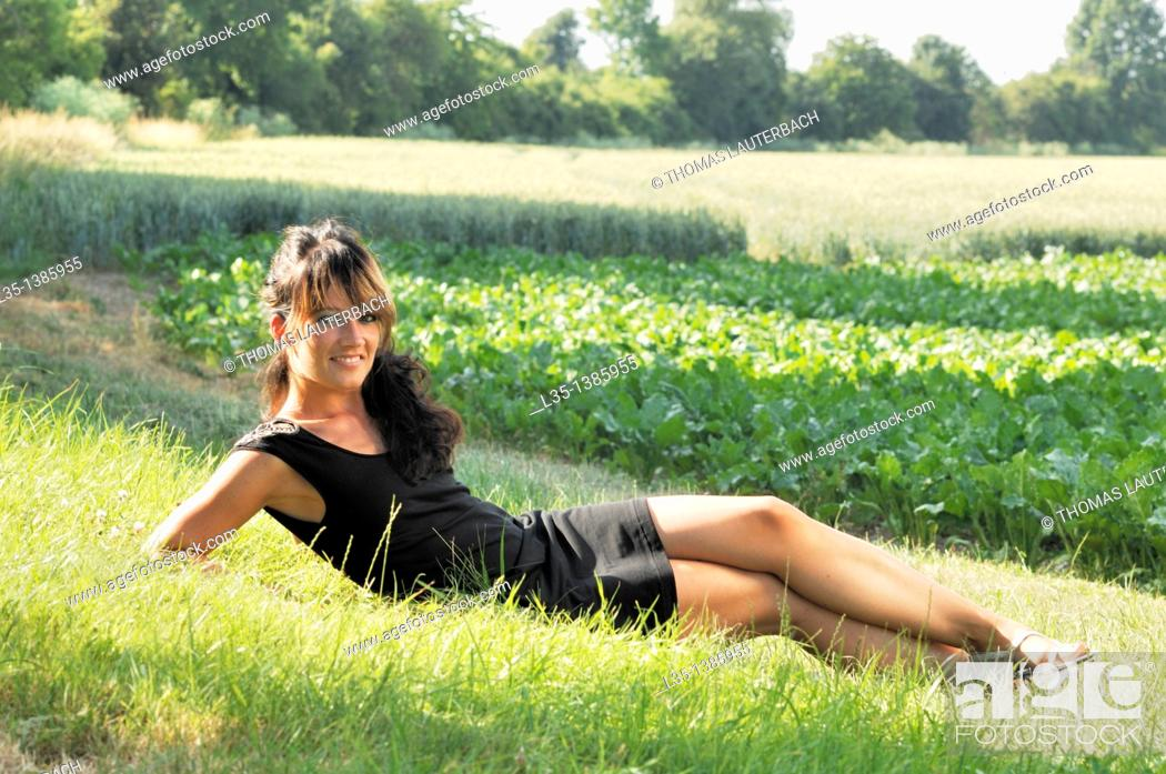Stock Photo: Young woman lying on the grass and relax, summer, Germany.