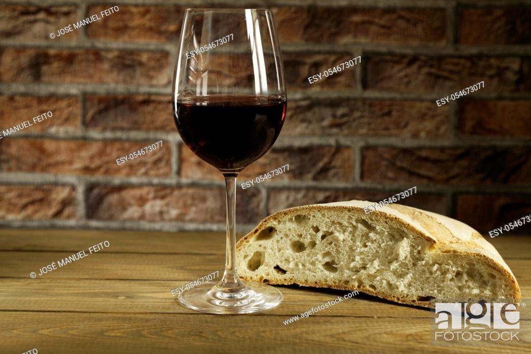 Stock Photo: Glass of red wine and a piece of rustic loaf of bread on wooden table and red brick background.