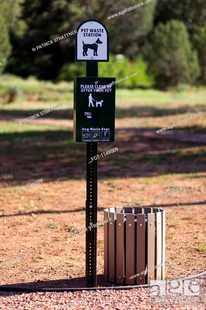 Stock Photo: A sign and bin for pet waste in a park.