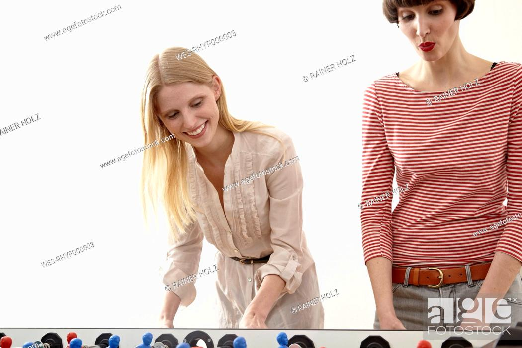 Stock Photo: Germany, Cologne, Young women playing table soccer, smiling.
