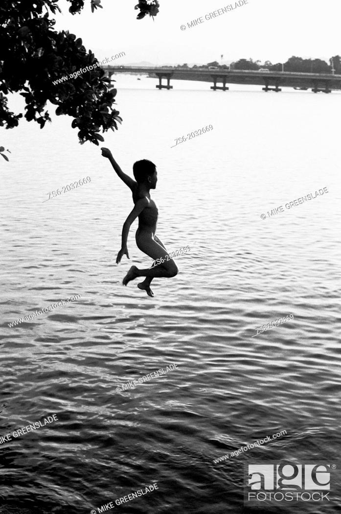 Stock Photo: Leaping boy, Huong River, Hue, Vietnam.