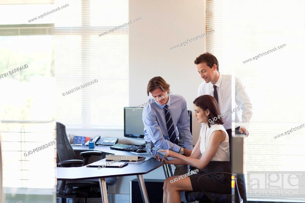 Stock Photo: Business people with digital tablet working in office.