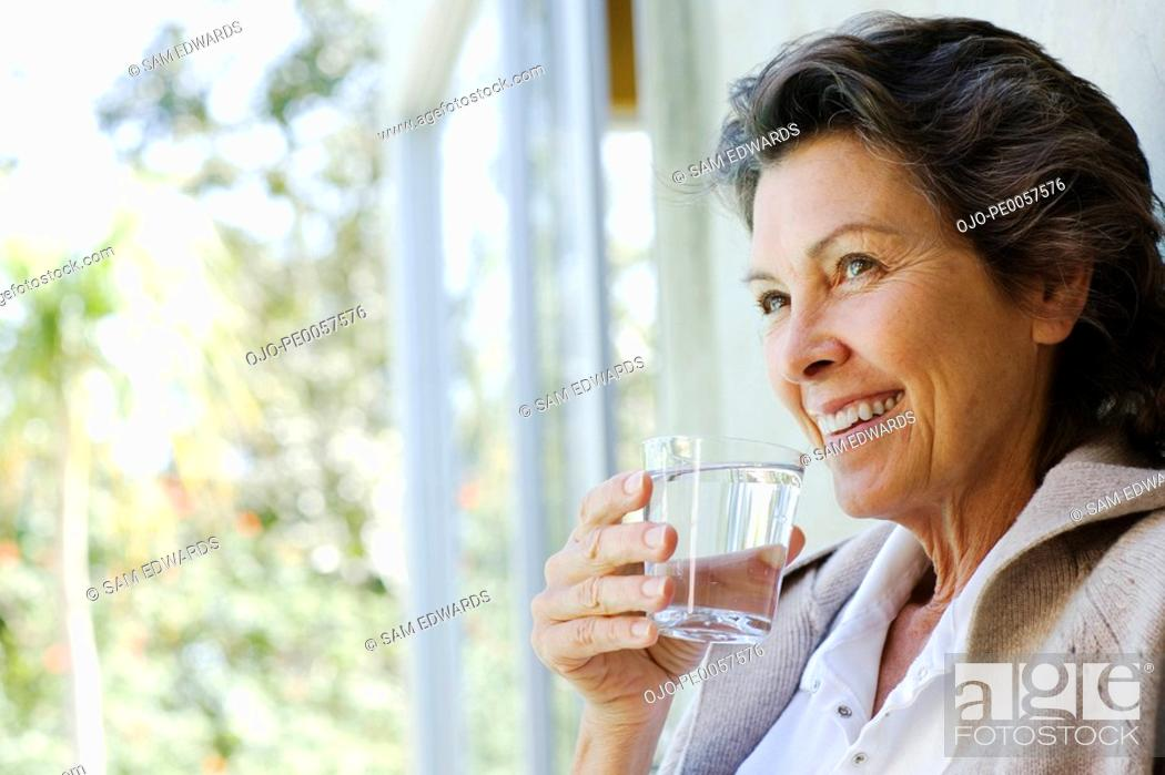 Stock Photo: Woman with glass of water standing in doorway.