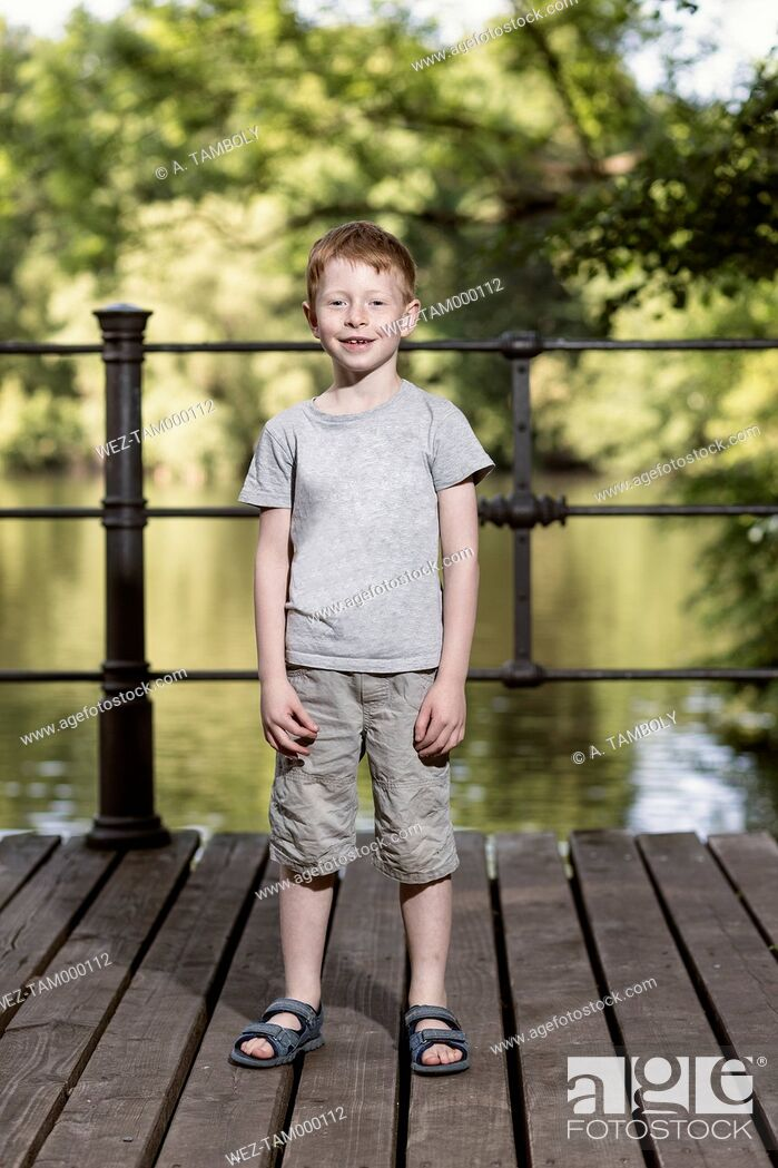Imagen: Portrait of little boy standing on footbridge in a park.
