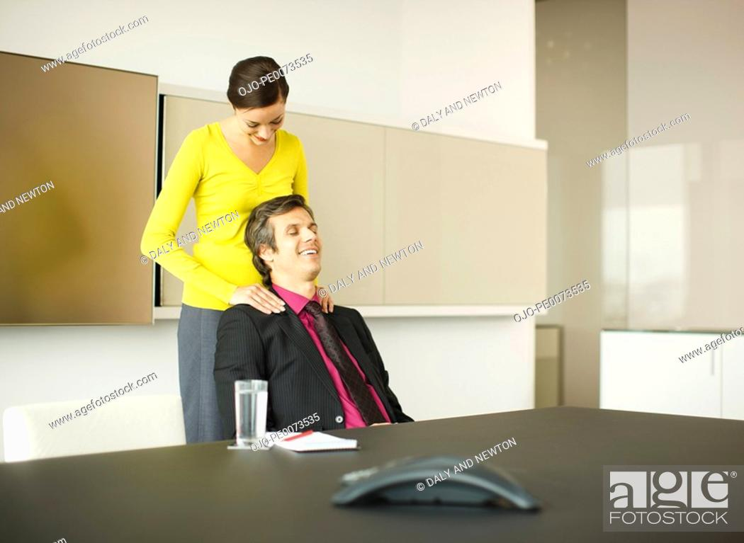 Stock Photo: Businesswoman rubbing businessman's shoulders in conference room.