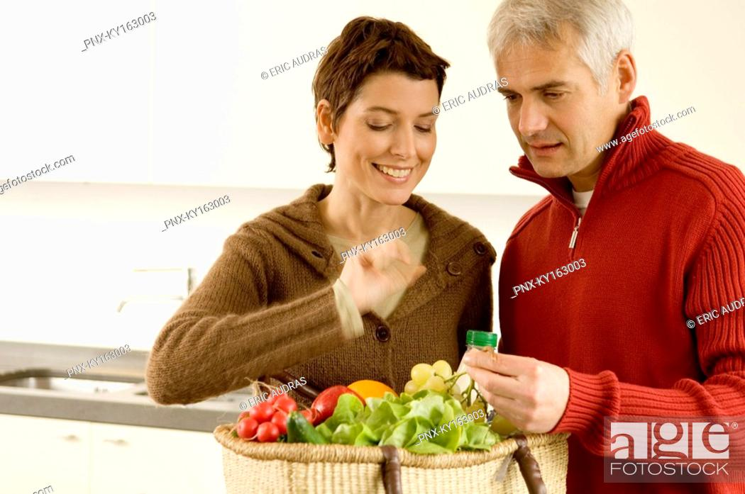 Stock Photo: Mature man holding a bunch of grapes with a mid adult woman standing beside him.