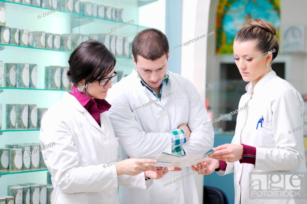 Stock Photo: team of pharmacist chemist woman and man group standing in pharmacy drugstore.
