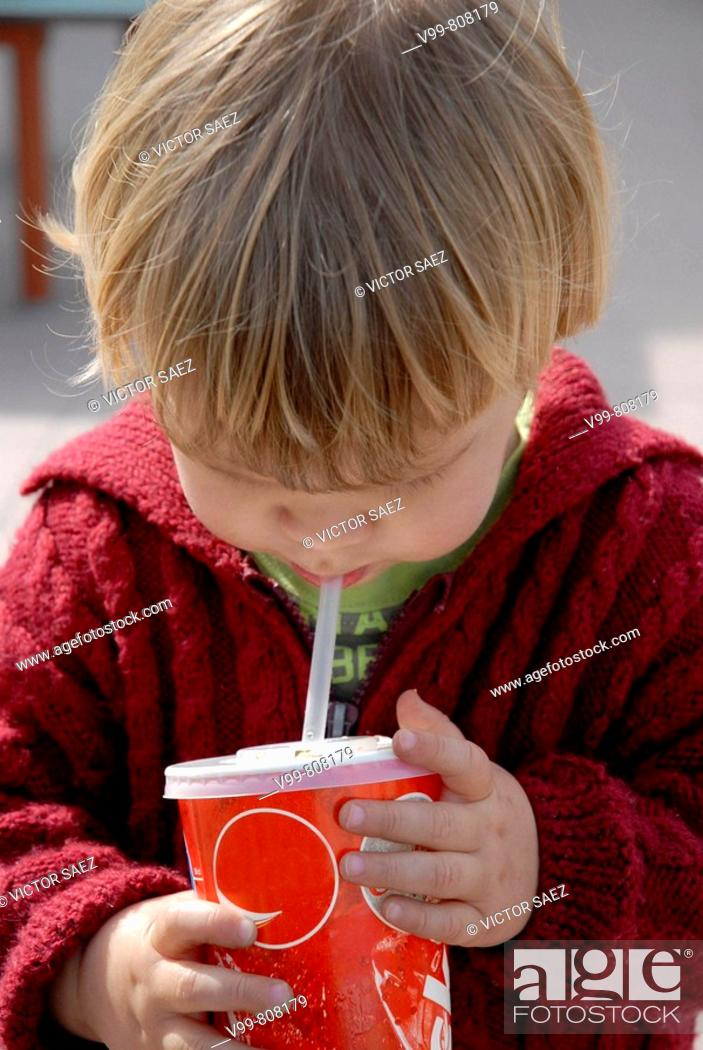 Stock Photo: 2 year old child who has a beverage timber straw.