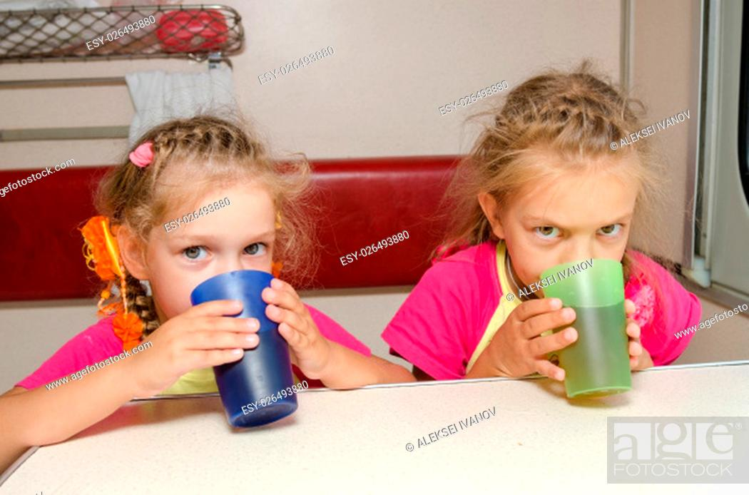 Stock Photo: Two children drink tea in train at the table on the lower place in the second-class compartment wagon.