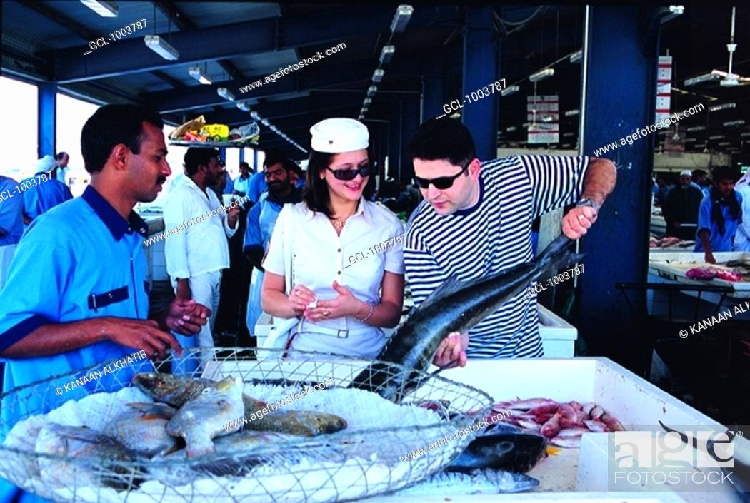 Stock Photo: Western tourists on the fish market in Dubai, UAE.